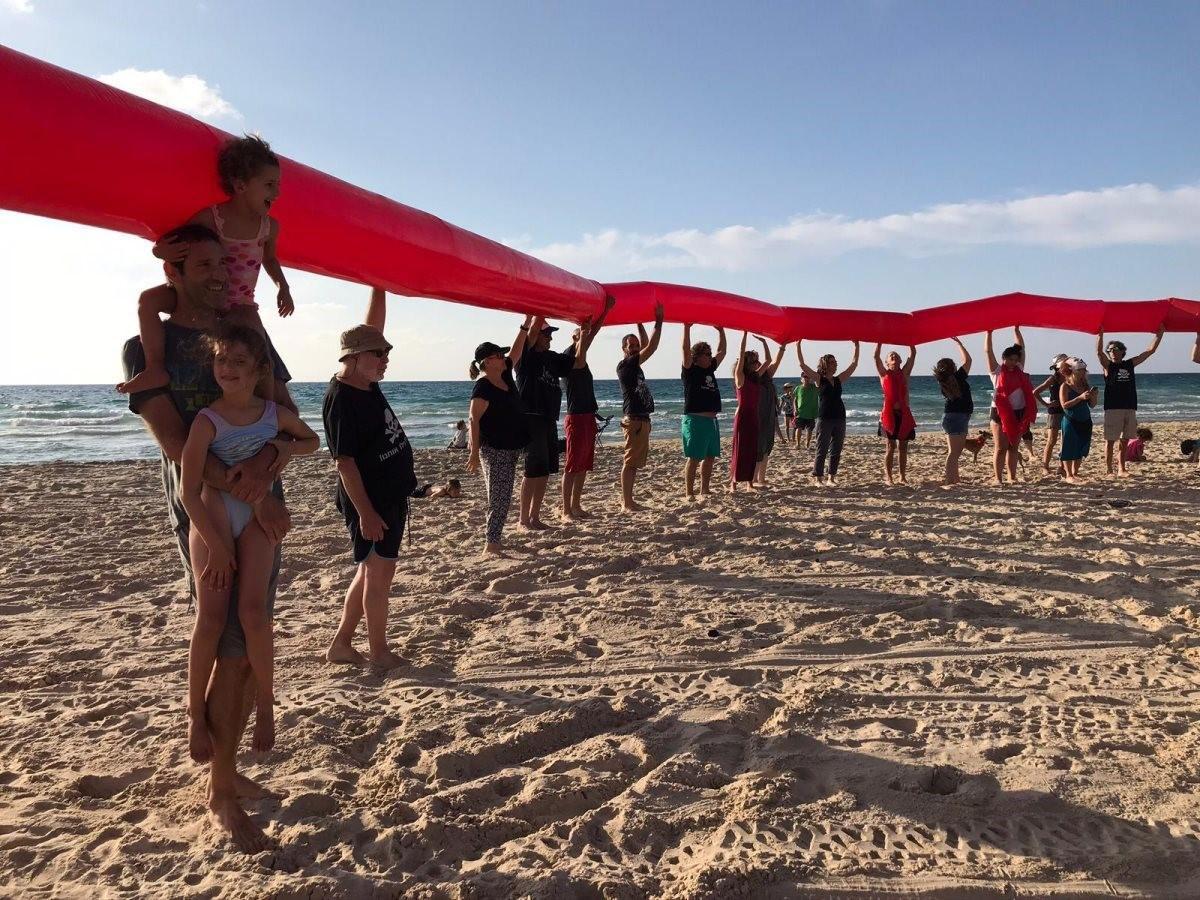 """נמשכת המחאה נגד עסקת קצא""""א עם האמירויות: שרשרת אנושית בחוף זיקים"""